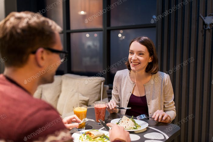 happy couple eating dinner at vegan restaurant