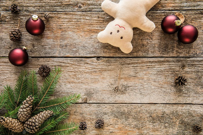 Christmas background. Ornaments, teddy bear and fir tree on wooden background