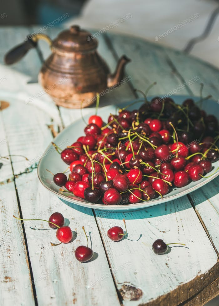 Plate of sweet cherries on light blue wooden table