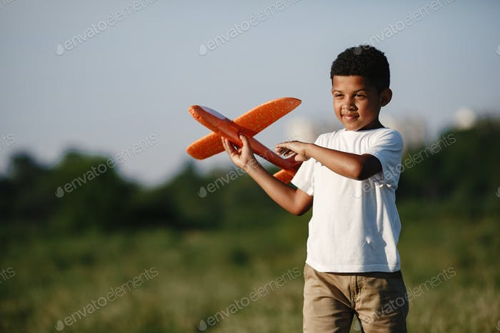 Little kid playing with airplane toy in green park