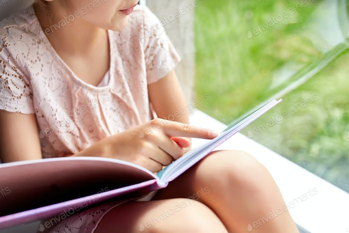Cute little girl reading book at home, at windowsill