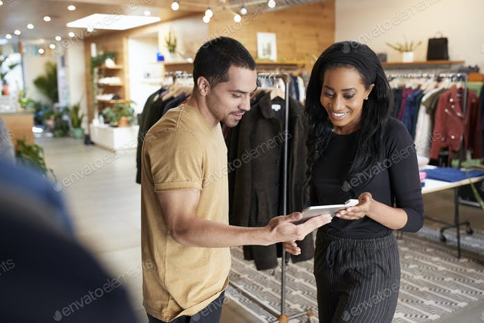 Smiling couple using tablet computer in a clothes shop