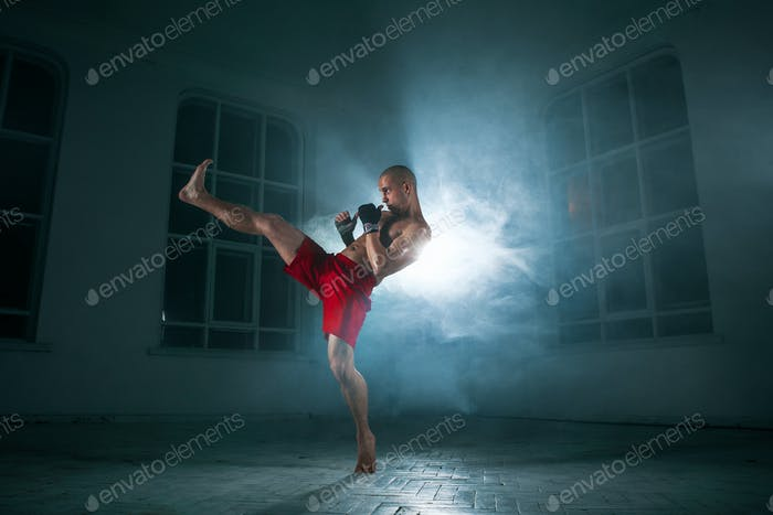 The young man kickboxing in blue smoke