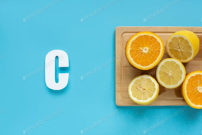 Top View of Ripe Cut Lemon And Orange on Wooden Cutting Board Near Letter C on Blue Background