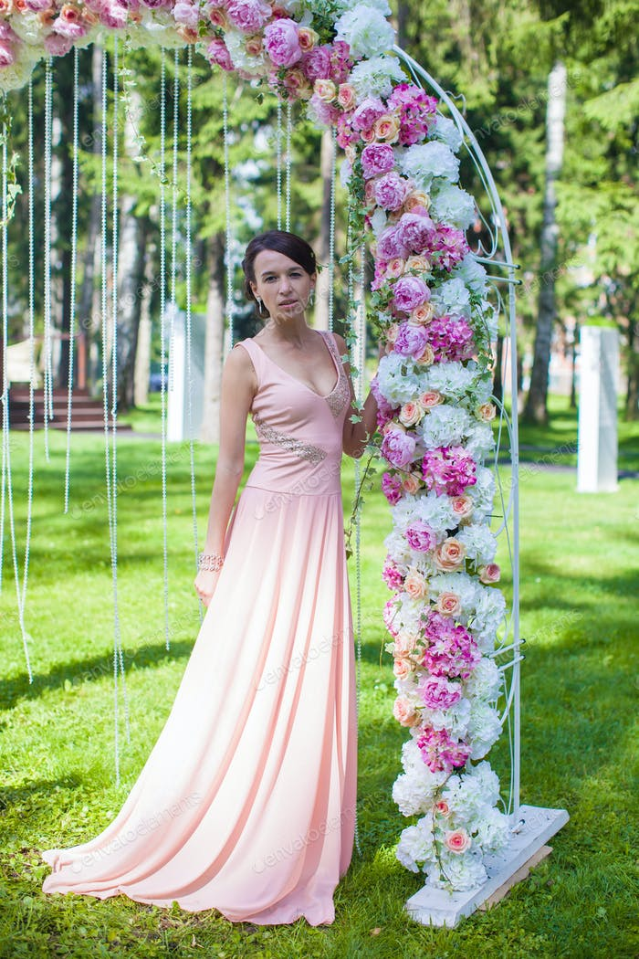 Beautiful charming young woman in wonderful dress at the ceremony outdoors