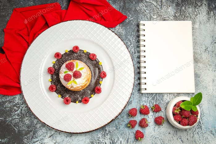 top view cake decorated with sugar powder raspberries and yellow particles on the base with