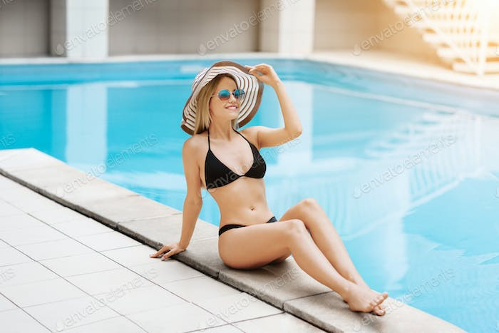 Caucasian girl in straw hat and swimsuit relaxing at poolside on summer vacation