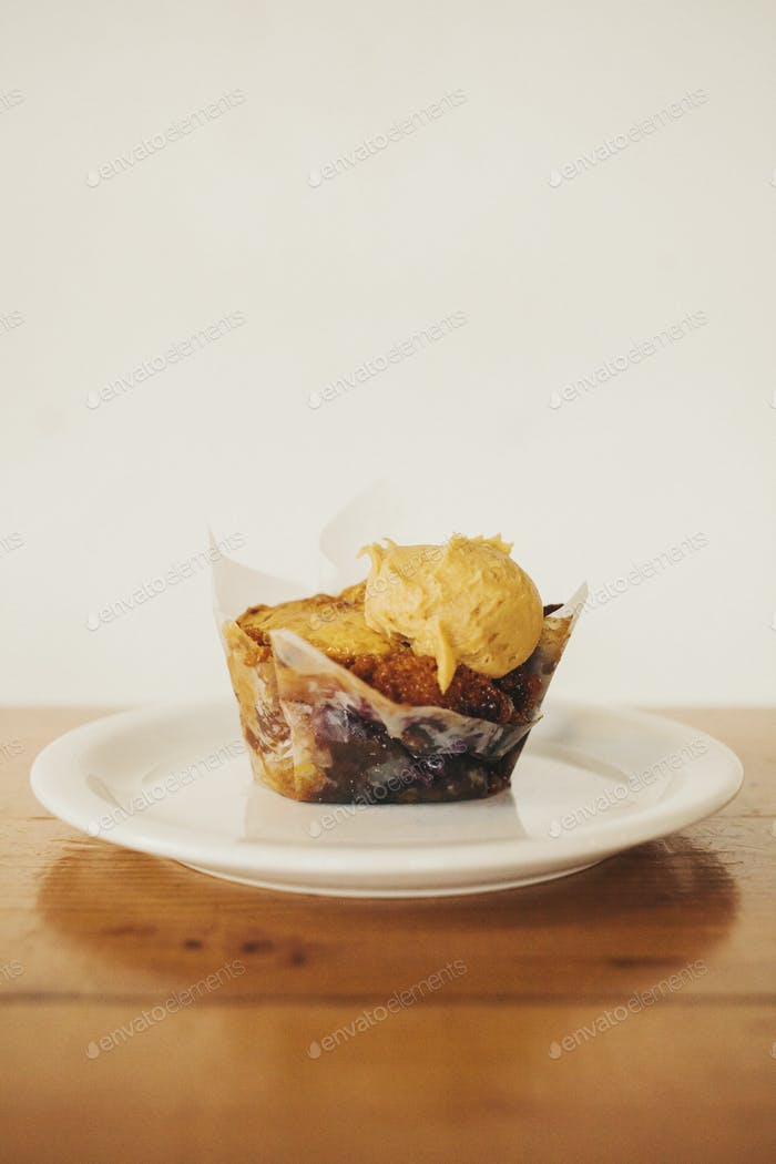 A fresh baked muffin with icecream on a plate.