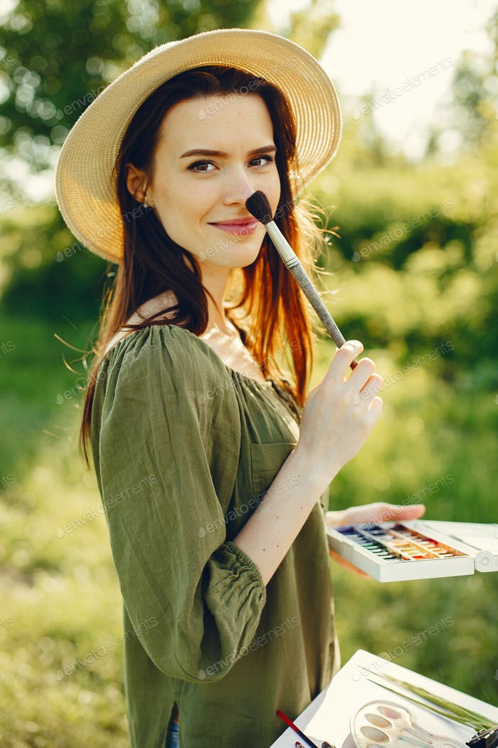 Elegant and beautiful girl painting in a field