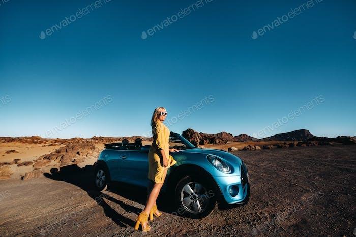 Frau genießen Roadtrip, stehend mit Karte in der Nähe von Cabrio-Auto am Straßenrand in der vulkanischen