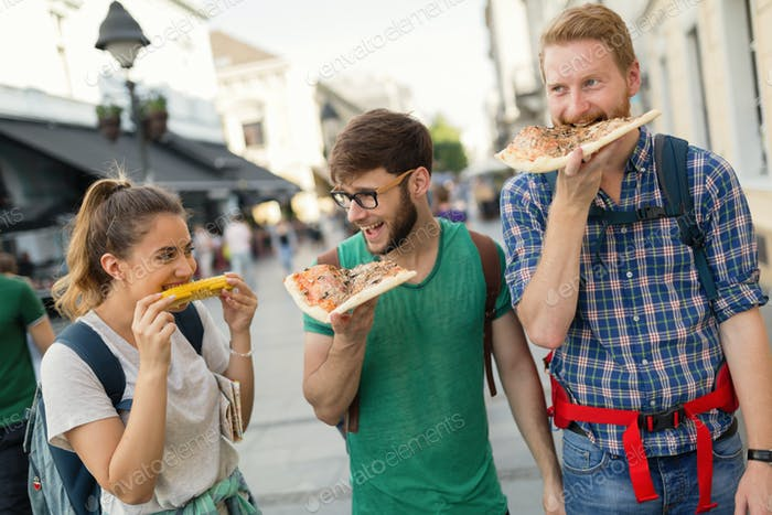 Happy group of people eating pizza outdoors