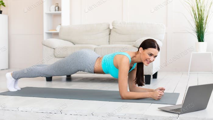 Young Woman At Laptop Exercising Doing Plank During Home Workout