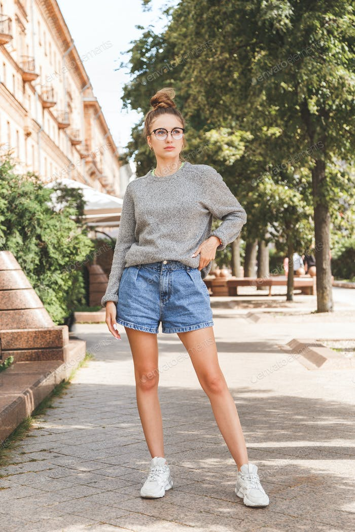 Street summer fashion portrait of young millennial girl in glasses and casual clothes
