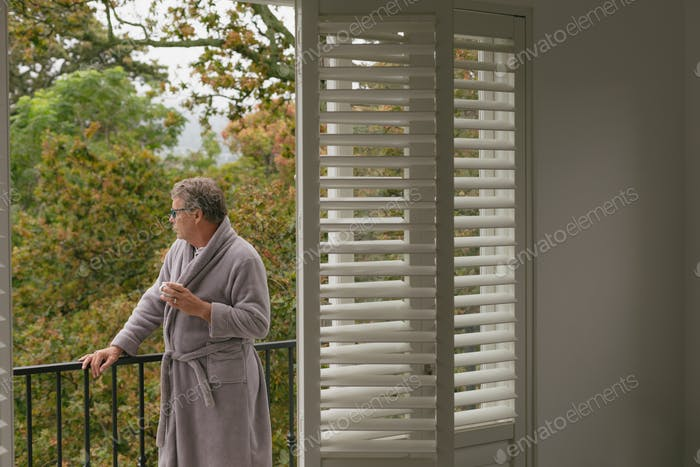 Thoughtful active senior Caucasian man with coffee cup standing in balcony in a comfortable home