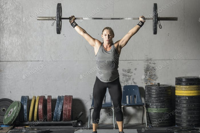 Strong woman with heavy barbell over her head.