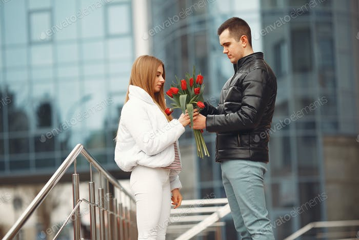 European couple is standing together with flowers