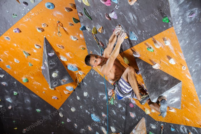 Young male rock climber in indoor climbing gym