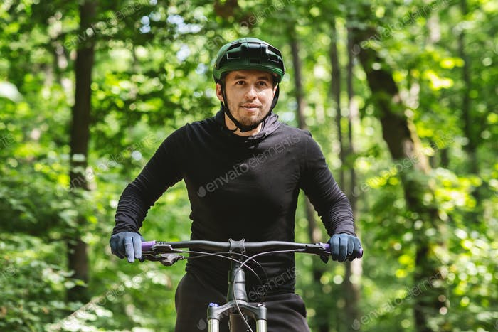 Excited cyclist looking forward over forest background