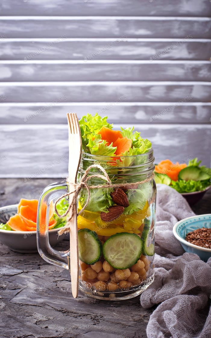 Vegetable salad with cucumber, pepper, almond and chick-pea in jar.
