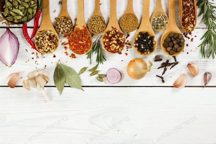 Various spices in wooden spoon on light background.