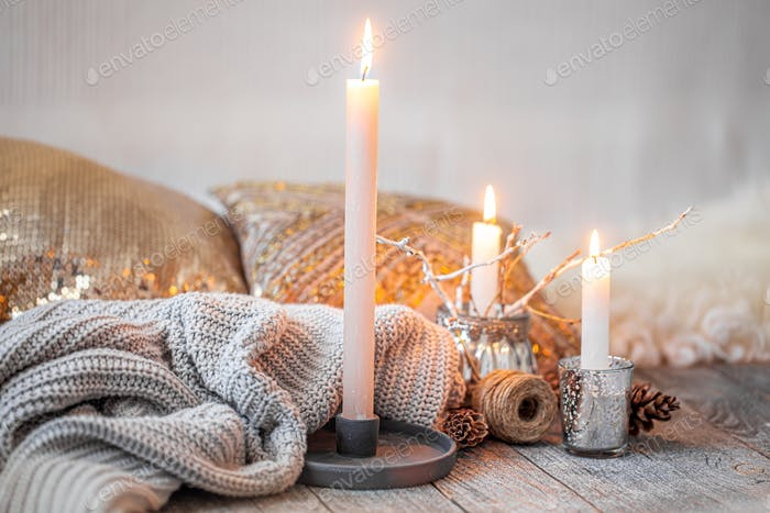 Cozy still life with burning candles and a knitted sweater.