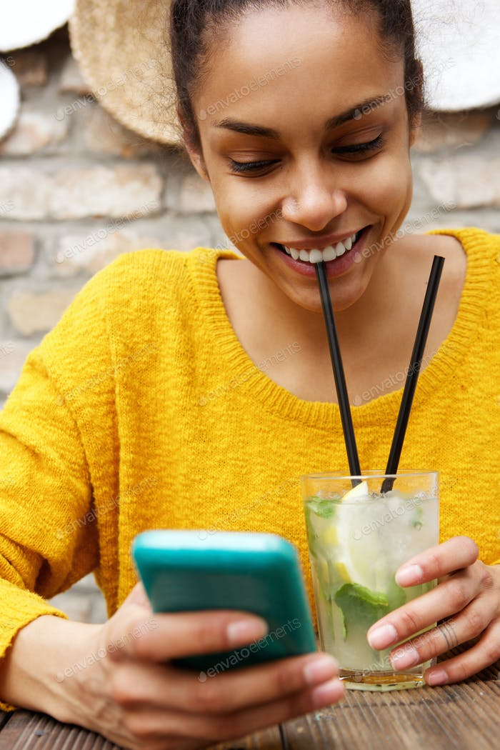Smiling woman drinking mojito and using mobile phone at cafe
