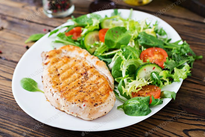 Grilled chicken breast and fresh vegetable salad - tomatoes, cucumbers and lettuce