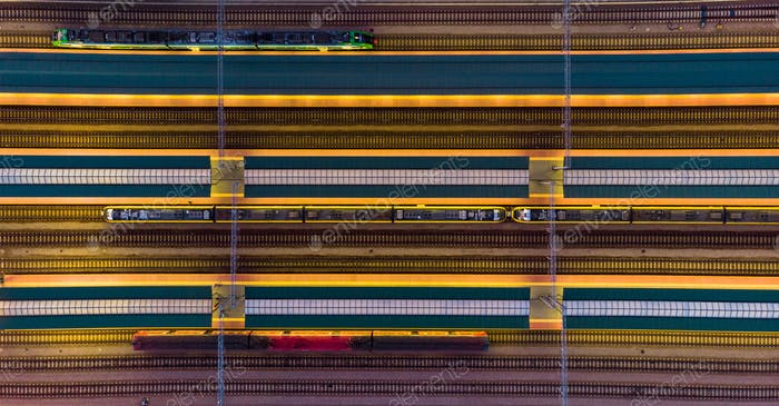 Illuminated platforms at rail station, top down aerial view