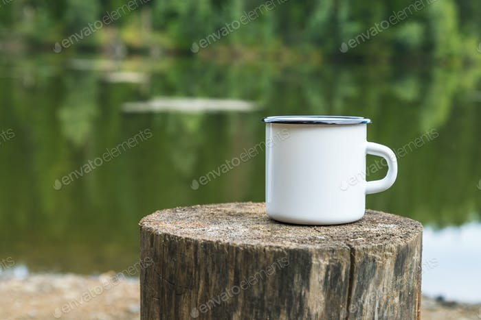 White enamel mug mockup with tree stump