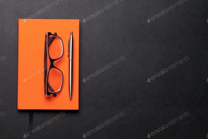 Büro-Arbeitstisch mit Gläsern und Zubehör