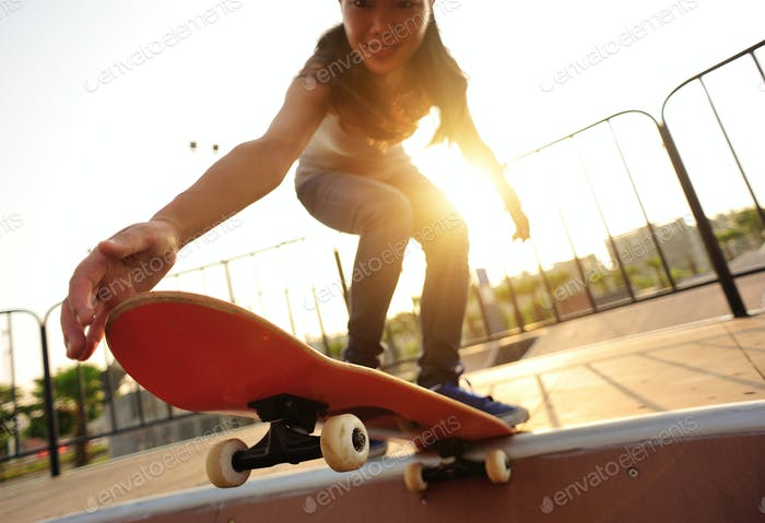 Skateboarder skateboarding at sunrise skatepark