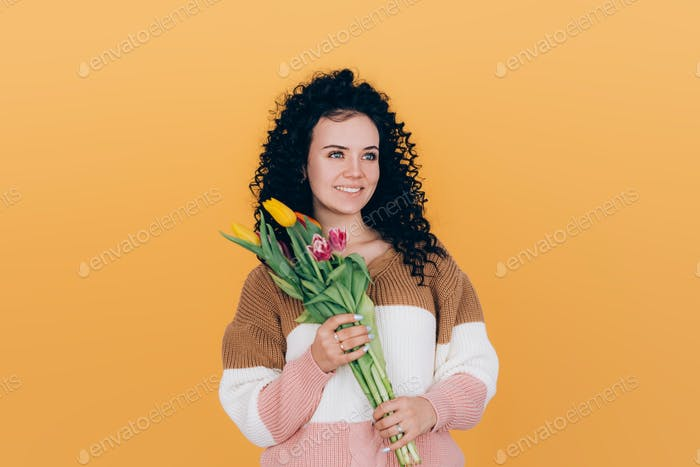 young beautiful young woman holding bouquet of tulips