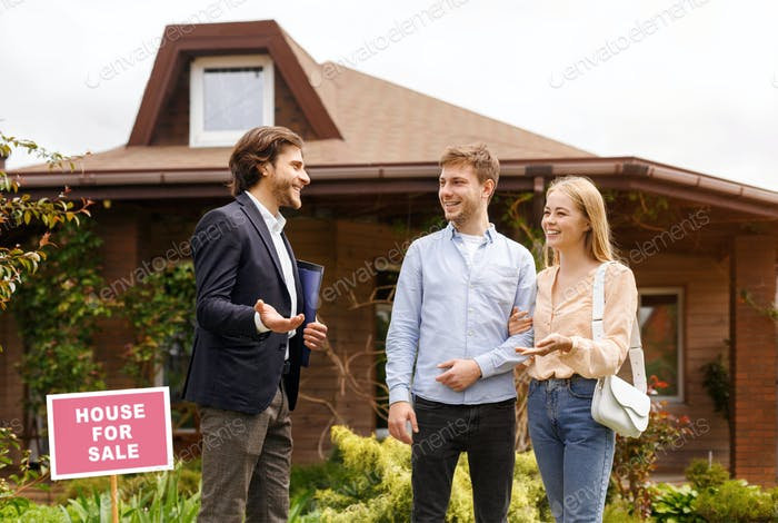 Young family talking to real estate agent about purchasing property near beautiful house outside