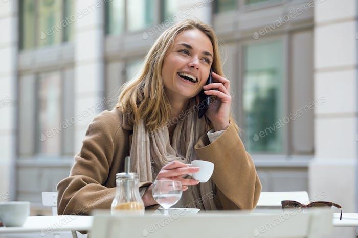hermosa joven mujer el uso de su teléfono móvil mientras beber taza de