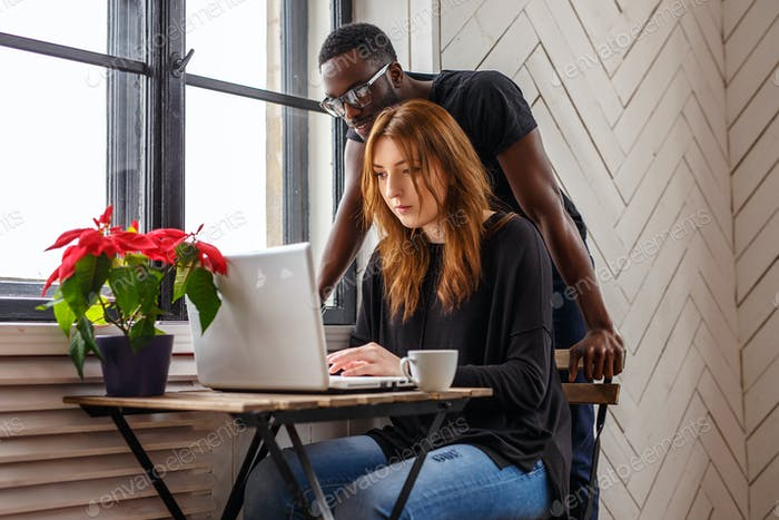 A black man and a woman warking with laptop.