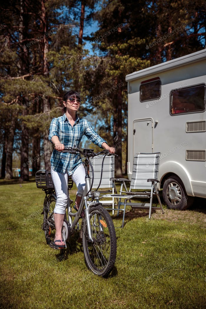 Woman on electric bike resting at the campsite VR Caravan car Va