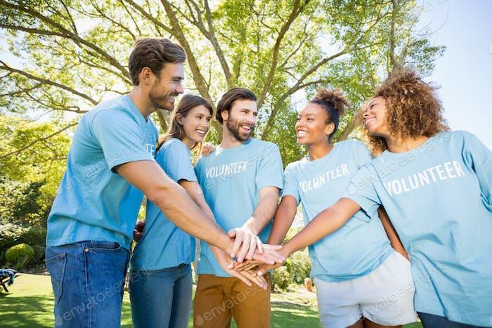 Grupo de voluntarios que forman las manos pila