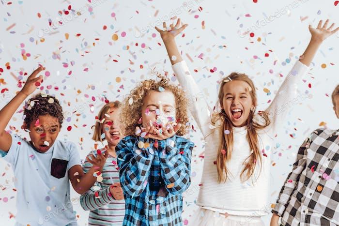 Kids in a room full of confetti