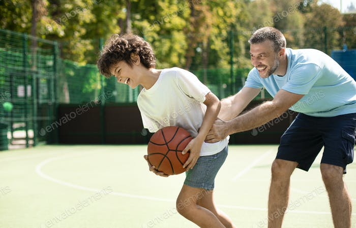 Sportive dad teaching his son how to play basketball