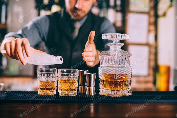 Close up of barman hands adding ice and whiskey to modern urban cocktails.