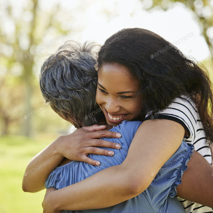 Senior Mother With Adult Daughter Hugging In Park
