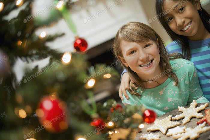 Two young girls with a tray of organic baked and iced Christmas cookies.