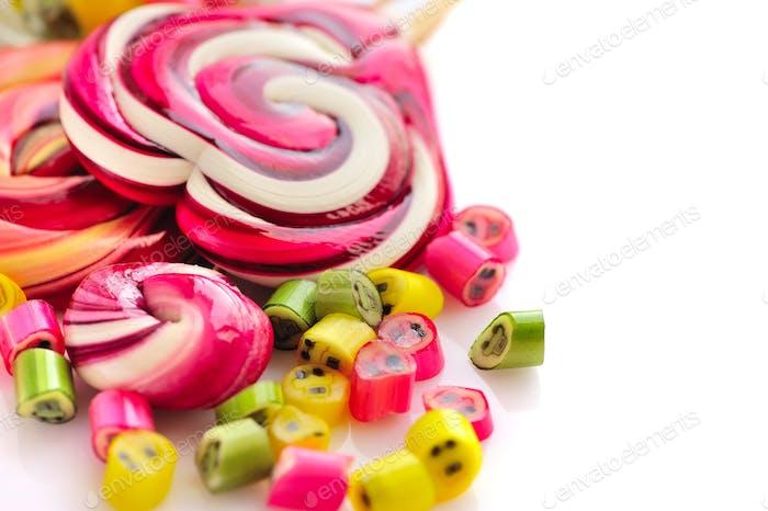 Bunte Süßigkeiten und Lutscher auf weißem Hintergrund