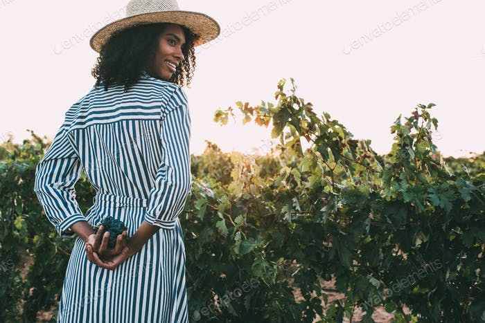 Woman standing in a path in the middle of a vineyard