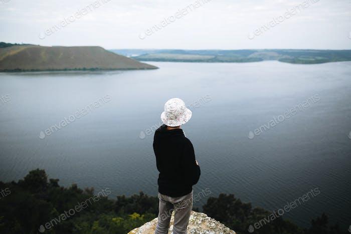 Hipster Teenager sitzt auf dem Felsenberg und Blick auf den Fluss