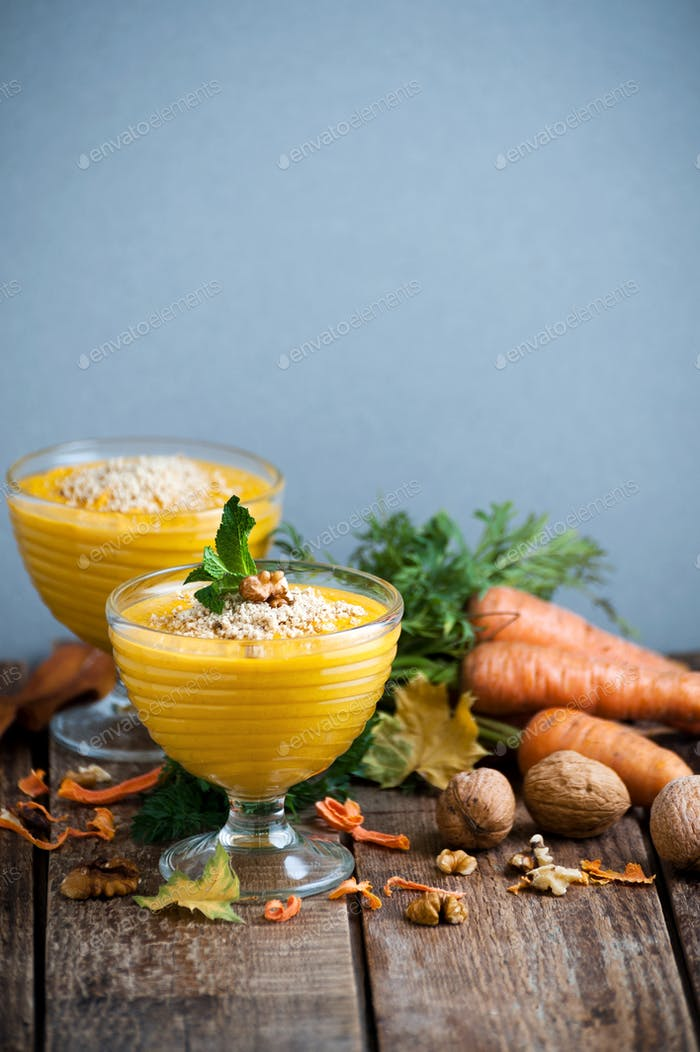 Carrot pudding with crushed nuts is served in glass bowls.
