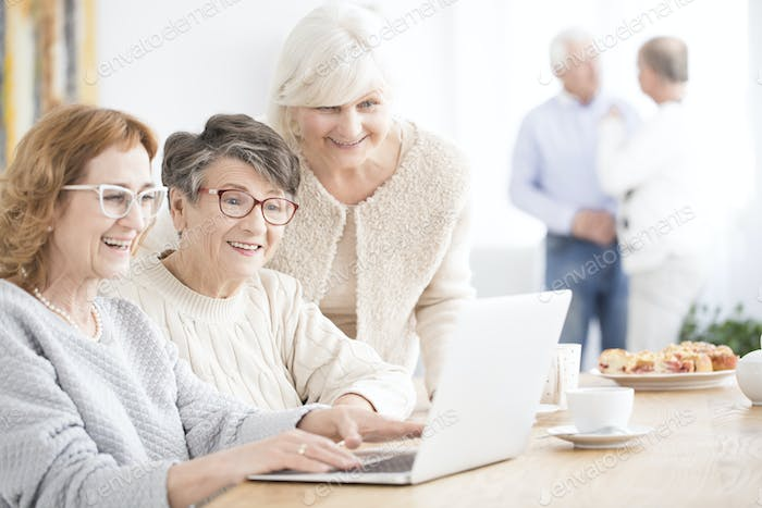 Smiling senior women using laptop
