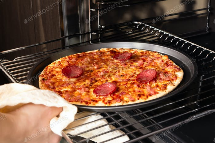 Woman taking out ready pizza out of the oven.