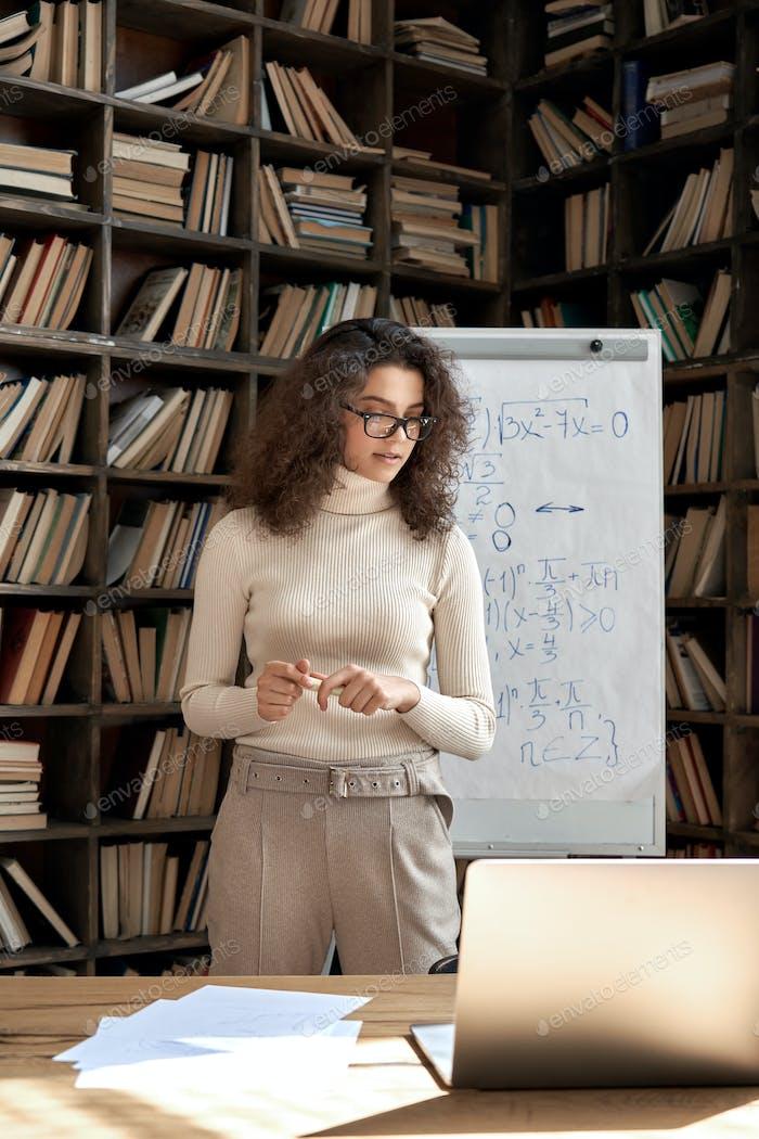 Profesora hispana trabajando en el aula con pizarra y portátil.