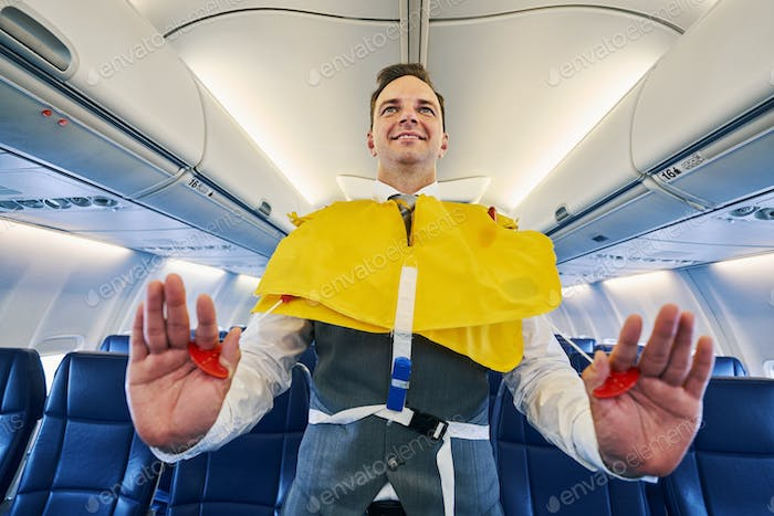 Smiling young steward inflating his the lifejacket aboard the aircraft